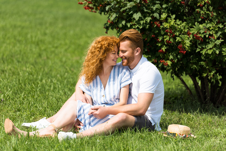smiling redhead coupe sitting face to face on grass in park