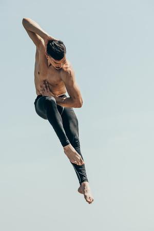 motion shot of handsome shirtless dancer in jump against blue sky