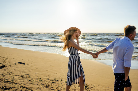 side view of young smiling couple in love holding hands on sandy beach in Riga, Latvia Stock Photo