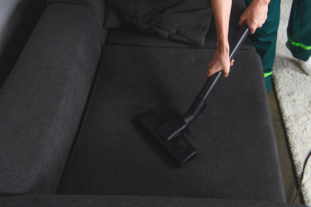 high angle view of person cleaning furniture with vacuum cleaner, upholstery cleaning Stok Fotoğraf