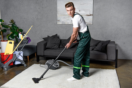 young professional cleaning company worker using vacuum cleaner Stock Photo