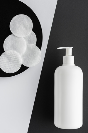top view of bottle of cream and cotton pads on black and white surface, beauty concept