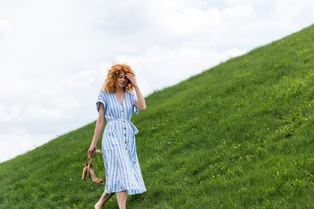 attractive redhead woman carrying shoes on grassy hill Stock fotó
