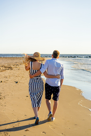 rear view of affectionate couple walking on sandy beach on summer day