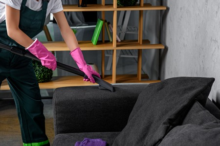 cropped shot of person in rubber gloves cleaning sofa with vacuum cleaner Stock Photo