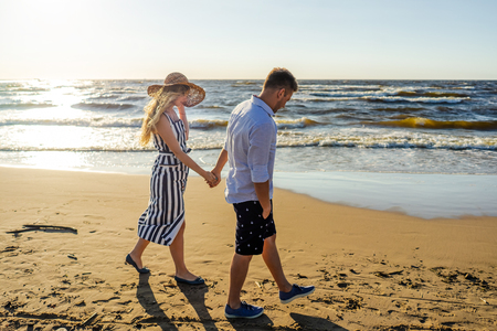 side view of young couple in love holding hands while walking on sandy beach in Riga, Latvia Stock Photo
