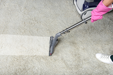 cropped shot of person cleaning white carpet with vacuum cleaner Stock Photo