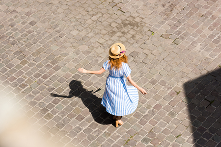 rear view of redhead woman in straw hat dancing at city street