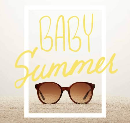 close up view of sunglasses on sand on grey background with baby summer symbol