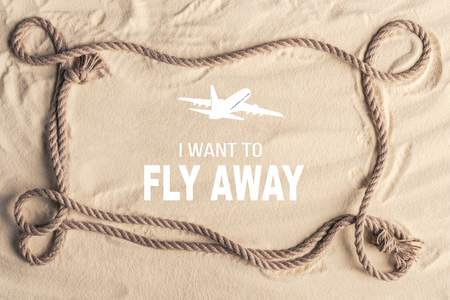 Frame of ship rope on sandy beach with I want to fly away lettering and airplane illustration