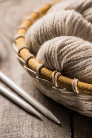 selective focus of beige knitted woolen yarn in wicker basket near knitted needles on wooden background Фото со стока - 106423287