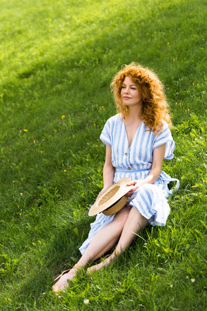 redhead attractive woman with straw hat in hands sitting on grassy meadow