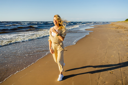 young smiling woman in stylish clothing walking on seashore on summer day Reklamní fotografie