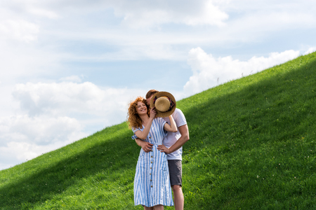 smiling redhead woman covering boyfriend face by straw hat on grassy hill