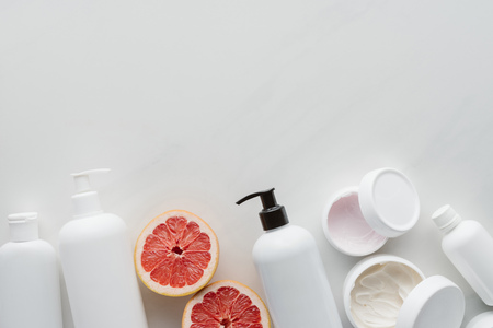 flat lay with containers of lotion and pieces of grapefruit on white surface, beauty concept Reklamní fotografie
