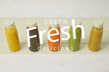 fresh organic smoothies in bottles standing in row on white, green fresh delicious inscription