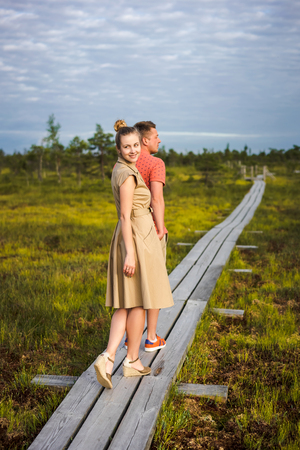 young couple in love holding hands on wooden bridge with green plants on background Foto de archivo - 106424237