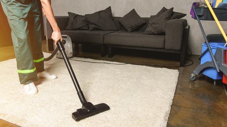 partial view of person using vacuum cleaner while cleaning white carpet