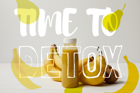 yellow detox smoothie in bottles with bananas, pears and kiwis on white background, time to detox inscription