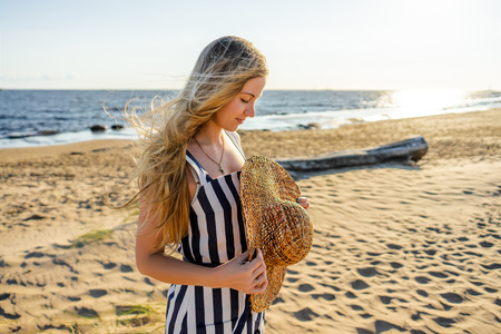 side view of attractive young woman with straw hat on sandy beach in Riga, Latvia Reklamní fotografie
