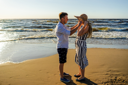 side view of young couple in love on sandy beach in Riga, Latvia Stock Photo