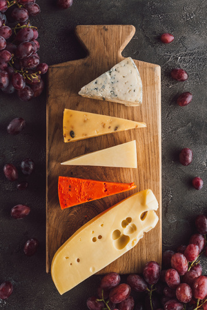 top view of assorted cheese on wooden cutting board with grape on dark surface 免版税图像