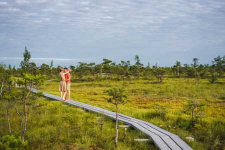 couple in love hugging on wooden bridge with blue sky and green plants on background Stock Photo