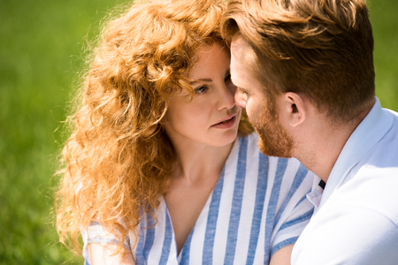 selective focus of redhead couple looking at each other outdoors