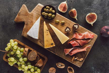 top view of assorted cheese and fruits on dark tabletop