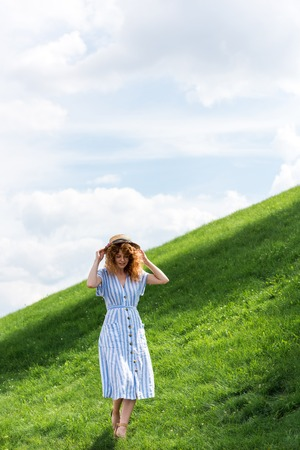 beautiful redhead woman in straw hat walking on grassy hill with blue sky behind
