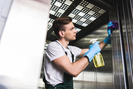 low angle view of handsome young cleaner washing elevator with rag and detergent Stock Photo