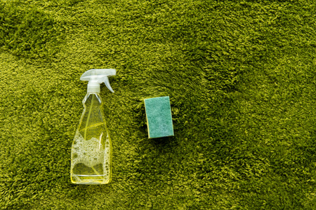 top view of spray bottle with detergent and rag on green carpet with copy space Stock Photo