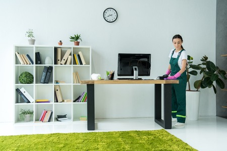 young cleaning company worker in rubber gloves and uniform cleaning desk in modern office Standard-Bild
