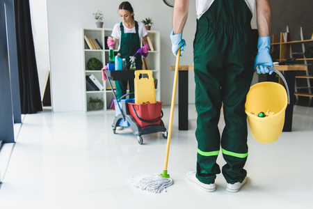 cropped shot of young cleaning company workers holding various cleaning equipment in office Stock Photo