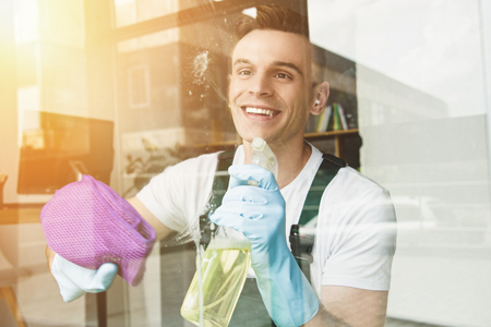 handsome smiling young man cleaning and wiping window with spray bottle and rag Stockfoto
