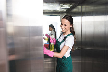 beautiful smiling young janitor cleaning elevator with detergent and rag Archivio Fotografico - 106426384