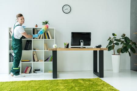 Limpiador joven guapo sonriendo a la cámara mientras limpia la oficina moderna