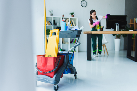 young female janitor cleaning office with various cleaning equipment