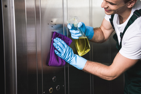 cropped shot of smiling young worker cleaning elevator with rag and detergent Imagens