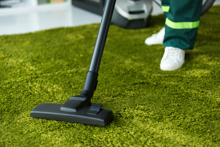 cropped shot of person cleaning green carpet with vacuum cleaner Stock Photo