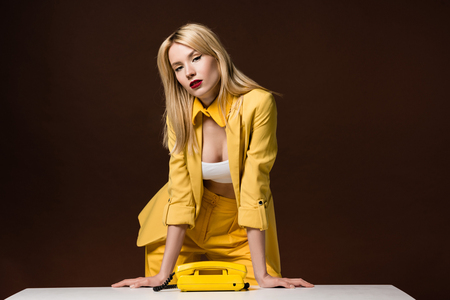 beautiful stylish blonde girl leaning at table with yellow rotary phone and looking at camera on brown