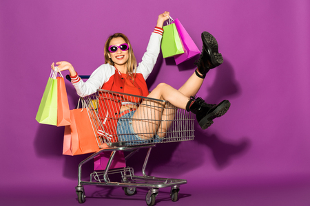 beautiful young woman in sunglasses holding shopping bags and sitting in shopping trolley on violet Foto de archivo