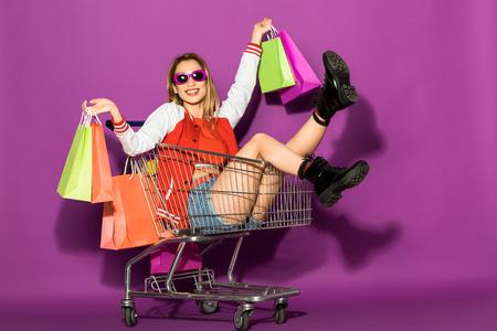Hermosa mujer joven en gafas de sol sosteniendo bolsas de la compra y sentado en el carrito de la compra en violeta