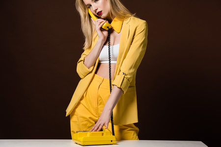 cropped shot of fashionable young woman talking by yellow vintage phone on brown Banque d'images - 106427012