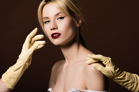 human hands in yellow gloves and sensual naked girl looking at camera on brown