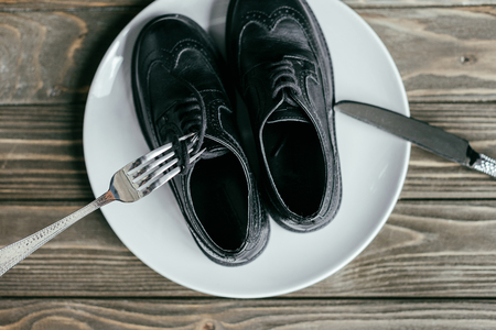 Top view of plate with black shoes and silverware