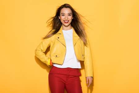 young asian female model posing on yellow background