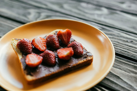 Bread with chocolate spread and strawberries on wooden table Banque d'images - 106427185