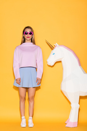 young stylish female model in sunglasses and decorative unicorn on yellow background