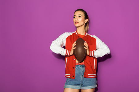 beautiful asian woman holding rugby ball and looking away isolated on violet